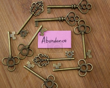 Photo pour Concept image à l'aide de vieilles clés et une étiquette avec le mot abondance manuscrite sur elle sur un fond en bois - image libre de droit