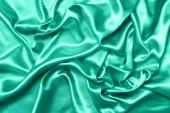"""Постер, картина, фотообои """"Крупный сделать рябь на шелковой ткани. Сатин текстильный фон. Зеленый цвет. Вид сверху. Цвет года 2020"""""""