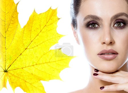 beauty portrait of attractive young caucasian woman brunette isolated on white studio shot lips face skin makeup eyes head and shoulders looking at camera hands nails yellow autumn leaves