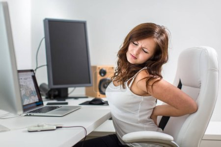 Photo for Young woman sitting at her computer desk suffering from acute back pain from her unhealthy sedentary lifestyle - Royalty Free Image