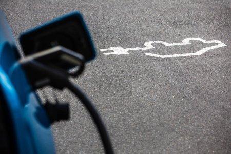 Photo pour Alimentation électrique pour la charge du véhicule électrique. Station de chargement du véhicule électrique. Gros plan du bloc d'alimentation branché à une voiture électrique en cours de charge. - image libre de droit