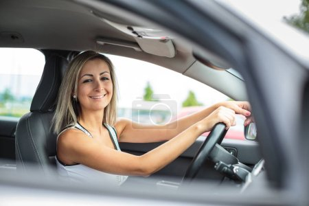 Photo for Woman driving a car - female driver at a wheel of a modern car, looking happy, smiling with a relaxed smile (shallow DOF; color toned image) - Royalty Free Image