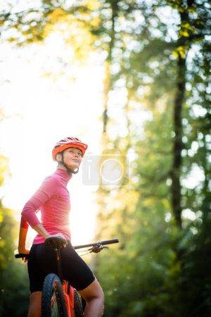 Foto de Pretty, young woman biking on a mountain bike enjoying healthy active lifestyle outdoors in summer (shallow DOF) - Imagen libre de derechos