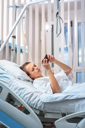 Photo pour Jolie, jeune, patiente dans une chambre d'hôpital moderne. S'améliorer rapidement après une intervention chirurgicale - coûteux mais positif, penser à l'avenir, faire des plans (peu profonde DOF ; image couleur tonique ) - image libre de droit