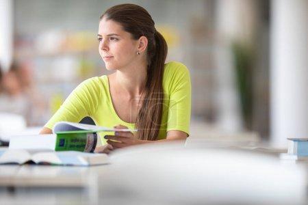 Photo pour Mignonne étudiante de l'université / lycée avec des livres dans la bibliothèque - image libre de droit
