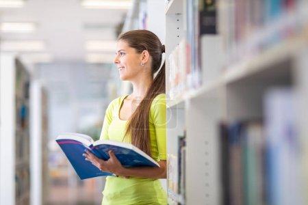 Mignonne étudiante de l'université / lycée avec des livres dans la bibliothèque