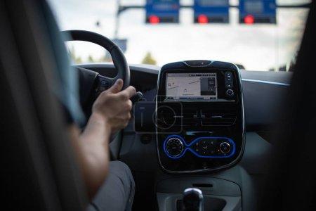 Photo pour Jeune homme conduisant un véhicule électrique dans un contexte urbain. Concept de covoiturage. Concept eCar. - image libre de droit