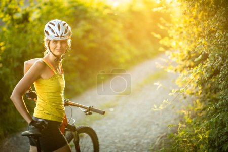 Photo for Pretty, young woman biking on a mountain bike enjoying healthy active lifestyle outdoors in summer (shallow DOF) - Royalty Free Image