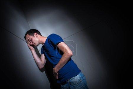 Hombre joven que sufre de dolor abdominal severo, siendo acorralado por la condición debilitante de la enfermedad celiaca / enfermedad de Crohn / enfermedad autoimune