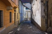 Zamocnicka paved street in historic part of Bratislava city, Slovakia with wall of old Franciscan Church