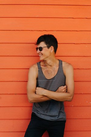 Photo for Happy handsome brunet in sleeveless shirt and sunglasses against orange house wall. Hands crossed on his chest. Religious necklace chain. - Royalty Free Image