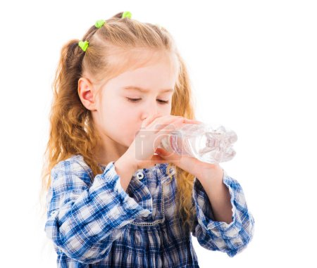 Photo for Child blonde girl drinks clean mineral water from transparent bottle isolated on white background - Royalty Free Image