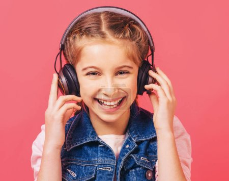 Photo pour Fille de gaie écoute de la musique avec un casque sans fil sur fond rose clair - image libre de droit