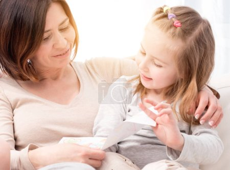 Photo for Happy smiling mom looking at the mothers day greeting card made by daughter sitting on sofa with little child - Royalty Free Image
