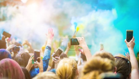 Photo for Crowd of people dancing and celebrating Holi festival of colors. People taking photos with mobile phones at color festival - Royalty Free Image