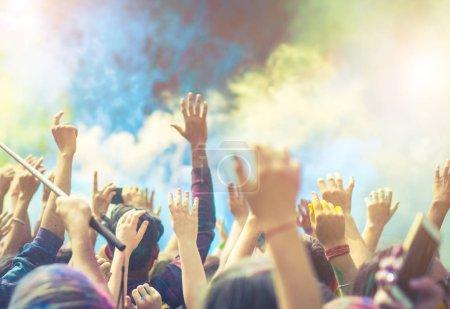 Foto de Multitud de personas bailando y celebrando el festival Holi de colores. Gente tomando fotos con teléfonos móviles en el festival a color - Imagen libre de derechos
