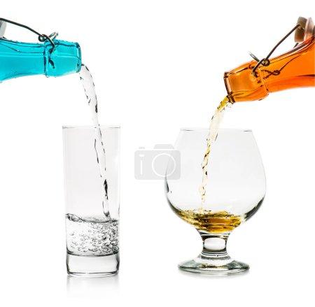 Füllen der Gläser mit Flüssigkeit aus blauen und orangen Glasflaschen isoliert