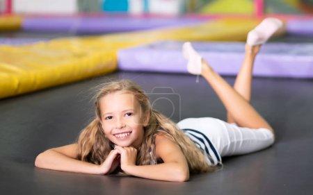 Foto de Pequeña chica bastante sonriente acostada en el trampolín negro - Imagen libre de derechos
