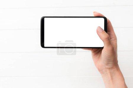 Photo pour Modèle d'utilisation du smartphone noir sur fond de table blanche pour votre conception - image libre de droit