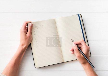 Photo pour Vue du dessus de la fille créant un plan dans un carnet sur une table blanche - image libre de droit