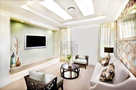 Foto de Este lujo salón tiene un sofá blanco con almohadones cerca de decoración de pintura de flores en la pared, hay dos sillas de madera con almohadones cerca de una mesa redonda con elementos decorativos cerca de la televisión - Imagen libre de derechos