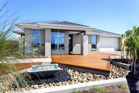 Photo pour Villa de luxe a yard en bois par le biais de la façade, il y a un garage avec plancher de béton ou de pierre. Maison jardin est principalement orné de pierres blancs noirs et grands brillants qui répand autour de l'étang Pierre, - image libre de droit