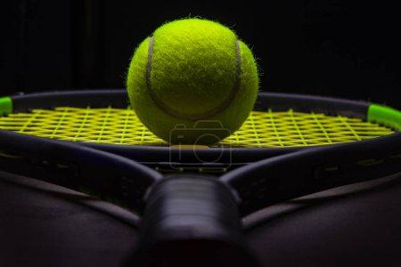 Photo pour Tennis balle et raquette fond sombre - image libre de droit