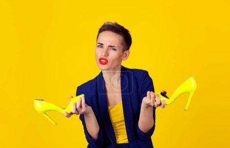 Photo pour Femme confus tenant paire de chaussures à talons hauts vous regardant perplexe demandant ce que vous voulez, je ne sais pas geste mains isolé sur fond jaune Modèle en costume bleu chemise jaune avec cheveux courts - image libre de droit
