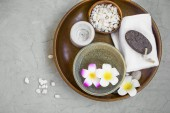 Spa products in wooden tray, top view of spa items with frangipani flowers, candle, bath salt, towel and ponce stone, spa still life setting
