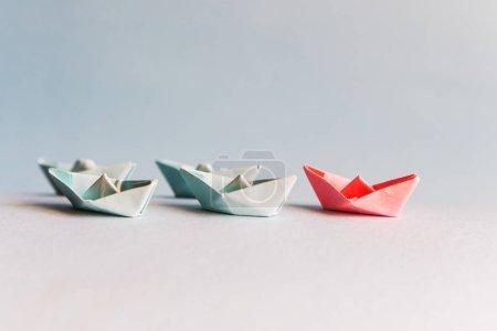 plusieurs bateaux en papier bleu et un rouge. Le concept de leader, succ