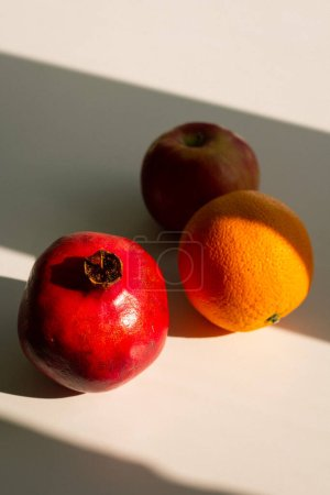 Photo for Fresh ripe pomegranate with oranges on light background, close view - Royalty Free Image