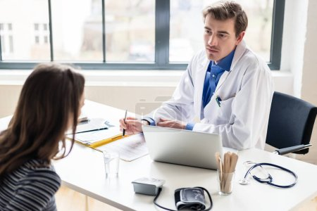 Young physician listening to his patient with respect and dedication