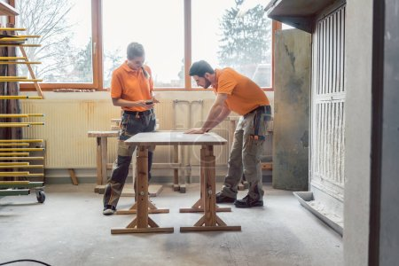 Team oft wo carpenters working on a table