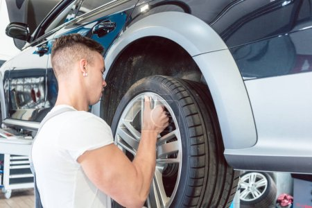 Skilled auto mechanic replacing the rims of a car in a trendy repair shop