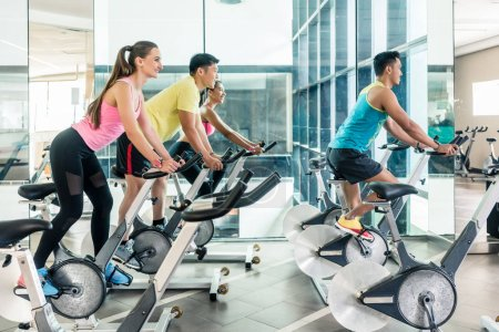 Fit women burning calories during indoor cycling class in the fitness club