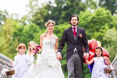 Wedding couple with flower children on bridge