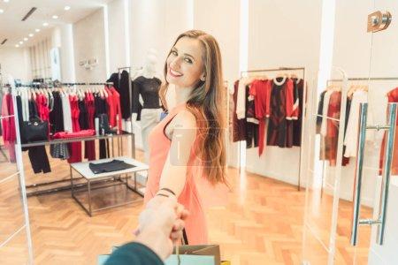 Женщина, перетащив ее мужчина моды, покупки в магазин или бутик