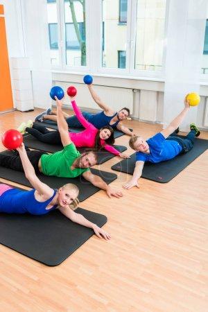 Photo pour Hommes et femmes au cours des exercices au sol sur des tapis d'yoga à l'aide de ballons au gymnase - image libre de droit