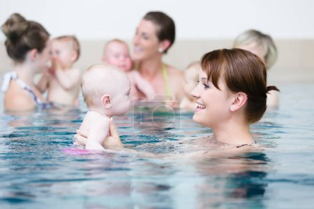 Group of mothers with children at baby swimming lesson