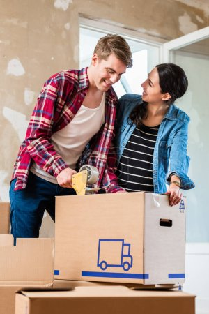 Young man and his girlfriend sealing a box while renovating their home