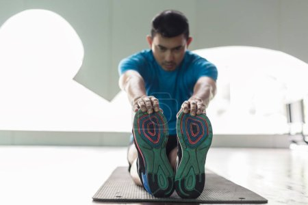 Man sitting down on exercise mat while touching his toes during stretching