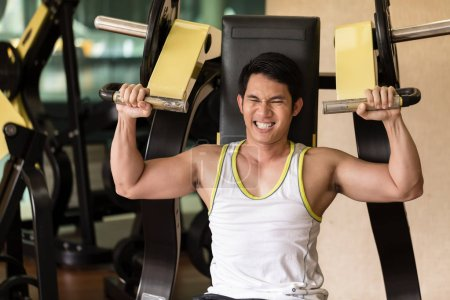 Strong young man exercising for arms muscles at a fitness club
