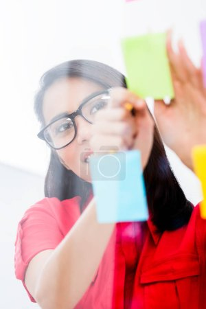 Young employee looking at multiple reminders while planning her work