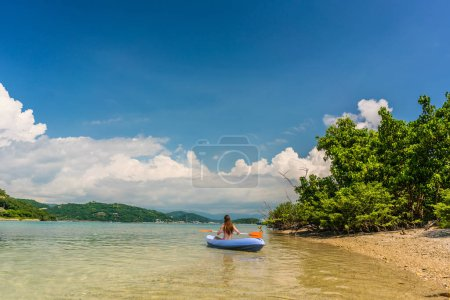 Young woman paddling during vacation in an idyllic travel destination