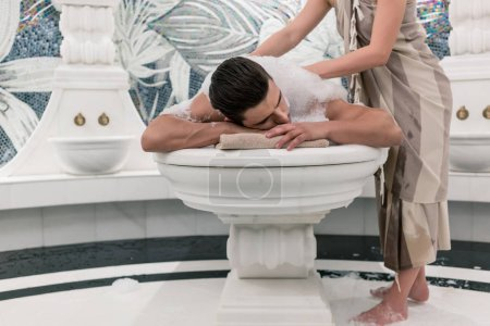 Relaxed man lying down on hot marble bed during traditional Turkish bath