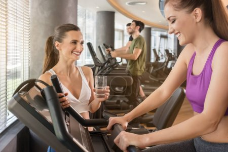Young woman helping her friend to set the parameters of treadmill