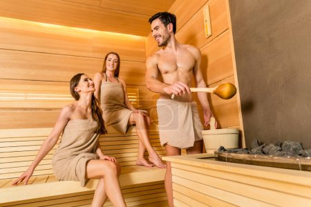 Photo for Full length of three young and beautiful people smiling while socializing in a wooden dry sauna heated with charcoals - Royalty Free Image