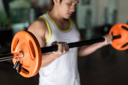 Determined young man holding a barbell while exercising bicep curls