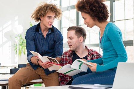 Photo pour Trois étudiants de partager des idées et des opinions tout en comparant les informations des deux manuels différents pendant la pause au Collège - image libre de droit