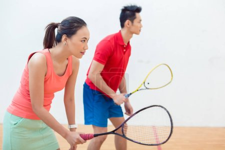 Competitive Chinese woman holding the racquet during a squash game